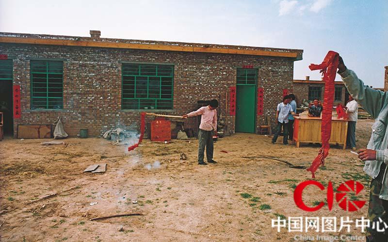 为祝福将要开始的新生活,张志民和儿子俊俊在新居门前放起了鞭炮。
