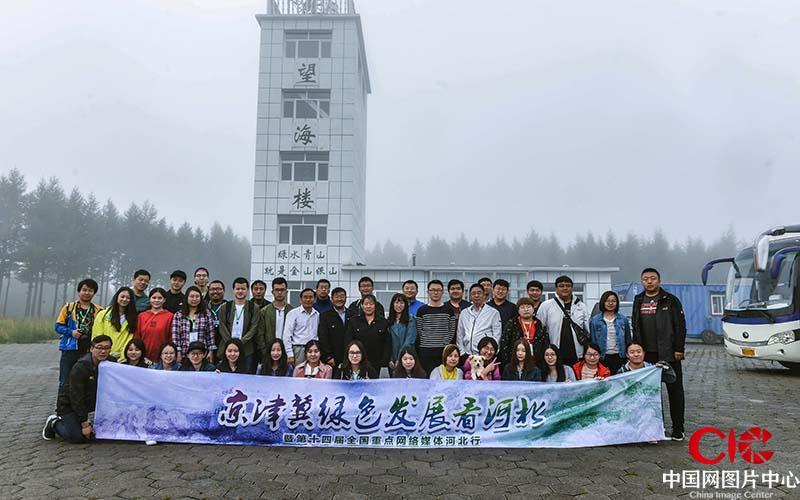 """在北京北部有一道""""绿色长城""""巍然矗立于山海之间,与蜿蜒于河北大地的古老长城交相辉映,展现着这片土地上新的绿色文明。在这片土地上,经过塞罕坝机械林场55年三代人前赴后继、艰苦卓绝,建成了世界上面积最大的人工林,成为首都和华北地区的水源卫士、风沙屏障,用生命书写了可歌可泣的绿色传奇。到2016年底,林场造林面积达到112万亩,成为世界上面积最大的人工林。图为京津冀绿色发展看河北媒体行人员与刘军齐淑艳夫妇在望海楼前合影"""